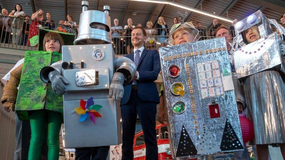 """Ministerpräsident Michael Kretschmer (CDU) it Kindern in Roboter-Kostümen, mit denen zusammen er das neue Erlebnismuseum """"ZeitWerkStadt"""" in Frankenberg eröffnet hat."""