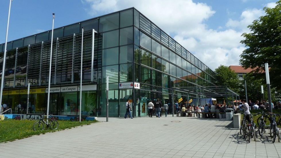 Die Cafeteria befindet sich im Erdgeschoss des Mensa-Gebäudes. Um mehr Platz zu schaffen, ist ein Reisebüro innerhalb der Ladenzeile bereits ein paar Meter weiter umgezogen.